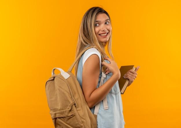 Aluna jovem e bonita sorridente, vestindo uma bolsa traseira em pé na vista de perfil, segurando o livro e olhando para trás, isolada na parede laranja