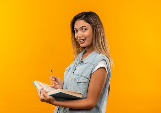 Aluna jovem e bonita sorridente, vestindo uma bolsa traseira em pé na vista de perfil, segurando um livro aberto e uma caneta isolada na parede laranja