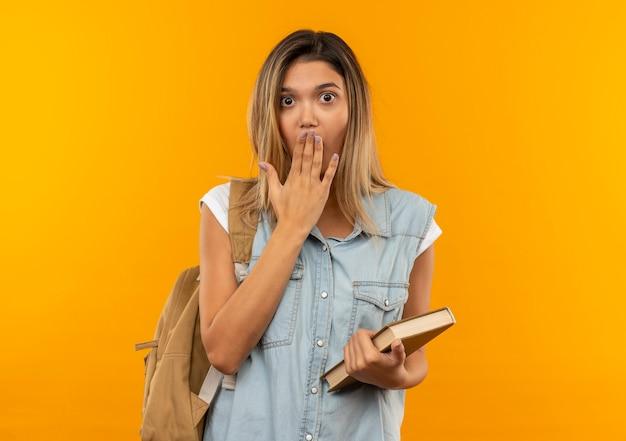 Aluna jovem e bonita surpresa com uma bolsa nas costas, segurando o livro e colocando a mão na boca, isolada na parede laranja