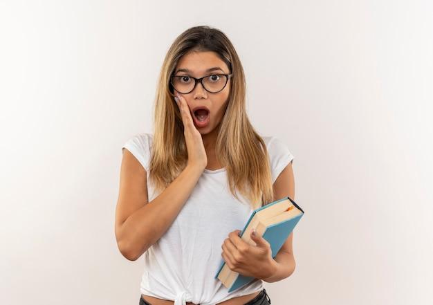 Aluna jovem e bonita surpresa de óculos e mochila segurando um livro e colocando a mão na bochecha isolada na parede branca
