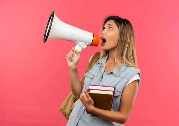 Aluna jovem e bonita vestindo uma bolsa de costas segurando livros, olhando para cima e falando por alto-falante