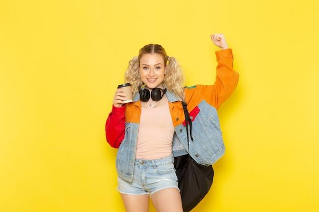 Aluna jovem em roupas modernas segurando café e flexionando no amarelo