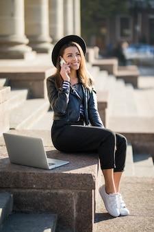 Aluna jovem empresária trabalha com seu computador laptop de marca no centro da cidade, sentada na escada de pedra em um dia ensolarado