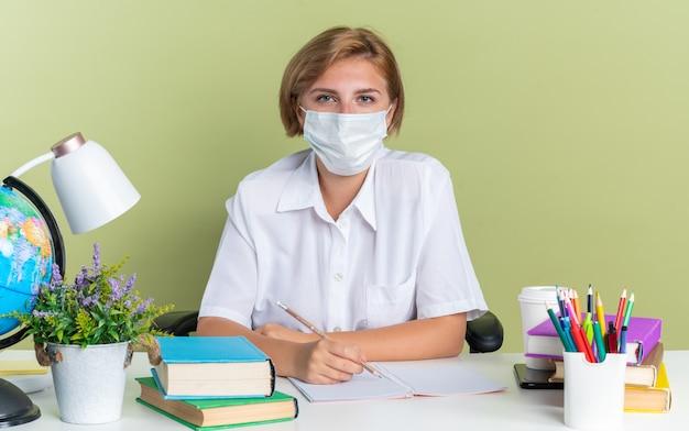 Aluna jovem loira séria usando máscara protetora sentada na mesa com ferramentas escolares segurando um lápis, olhando para a câmera isolada na parede verde oliva