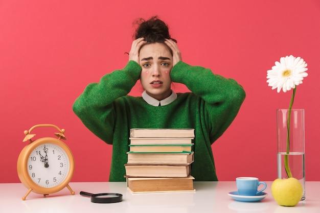 Aluna jovem nerd preocupada segurando a cabeça enquanto está sentada à mesa com livros