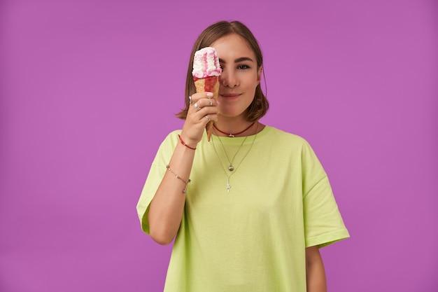 Aluna, jovem senhora com sorvete. segurando o sorvete sobre o olho. vestindo camiseta verde, pulseiras, anéis e colar