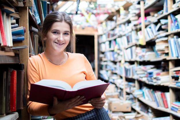 Aluna lê um livro na biblioteca antiga, uma mulher está procurando informações nos arquivos