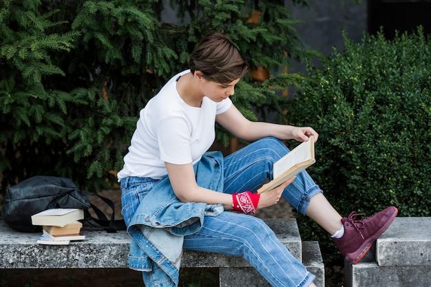 Aluna, lendo o livro no parapeito do parque