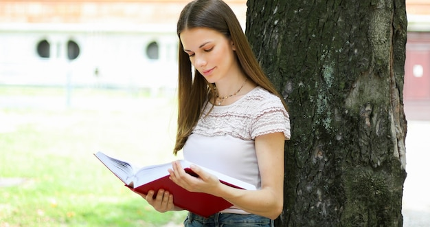 Aluna, lendo um livro, ao ar livre, parque, mentindo, contra, um, árvore, e, sorrindo