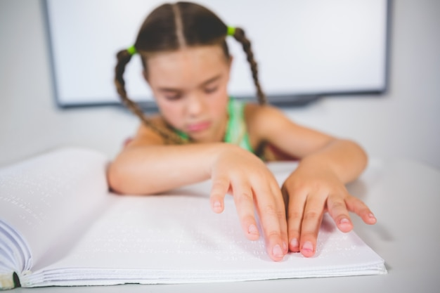Aluna lendo um livro em braille na sala de aula