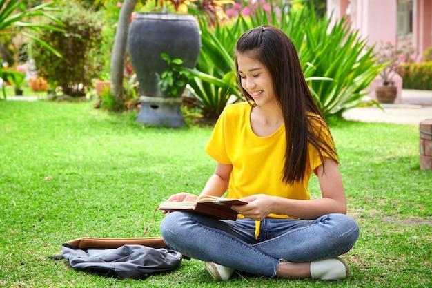 Aluna lendo um livro no parque