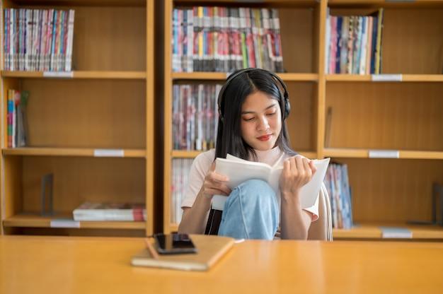 Aluna ler um livro na biblioteca