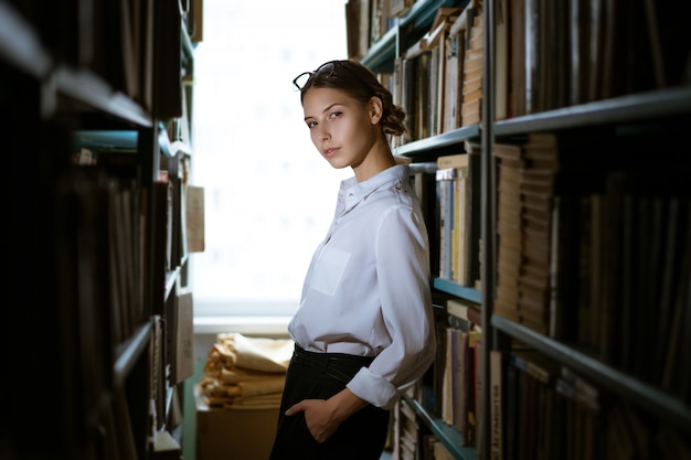 Aluna linda camisa fica entre as linhas da biblioteca, estantes de livros. foto escura