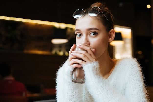 Aluna linda com um suéter branco bebe cappuccino em um café