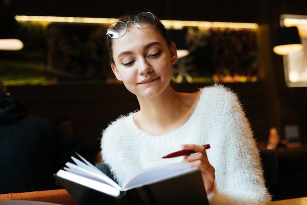 Aluna linda com um suéter branco sentada em um café, escrevendo em seu caderno