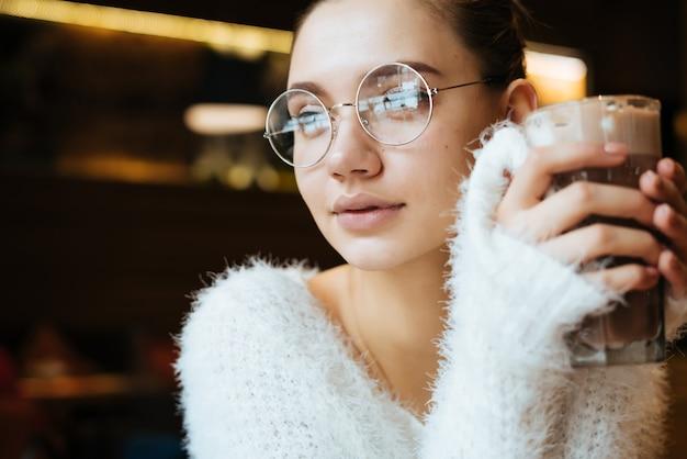 Aluna linda de jovem usando óculos e uma jaqueta branca, sentada em um café e bebendo um delicioso café com leite