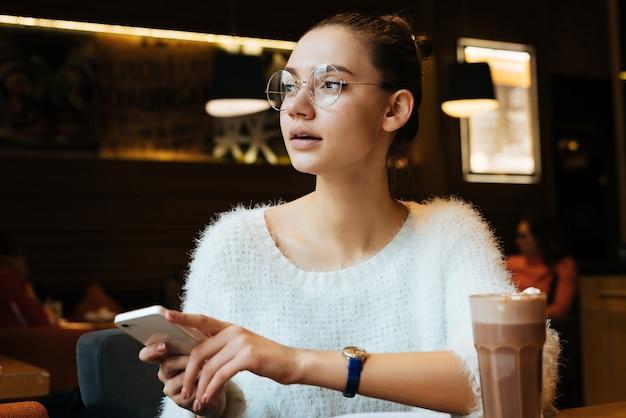 Aluna linda de jovem usando óculos, sentada em um café, bebendo cappuccino depois da escola, segurando o smartphone nas mãos e olhando pela janela