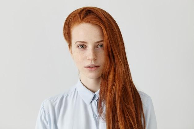 Aluna linda e ruiva com um penteado comprido e solto usando uma camisa formal azul-clara