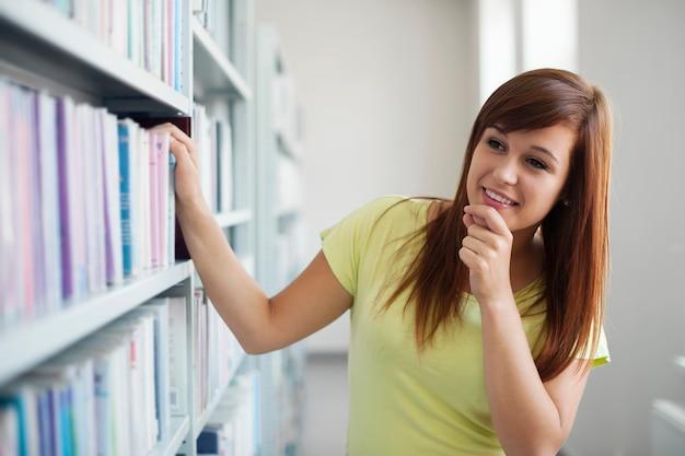 Aluna linda escolhendo livro na biblioteca