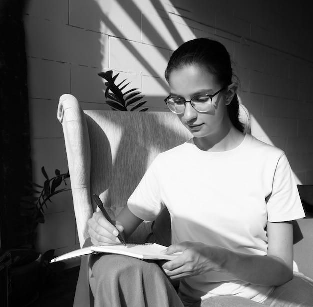 Aluna linda escreve com uma caneta uma tarefa em um caderno enquanto está sentado em uma poltrona em um café com elegantes sombras diagonais, luz forte, preto e branco.