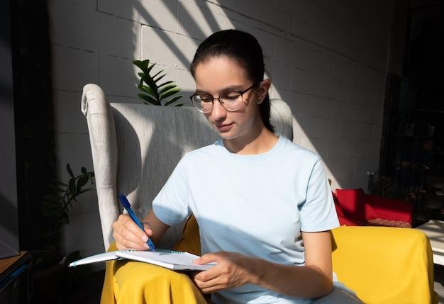 Aluna linda escreve com uma caneta uma tarefa em um caderno enquanto está sentado em uma poltrona em um café com sombras diagonais elegantes, luz forte. de volta ao conceito de escola. conceito freelance