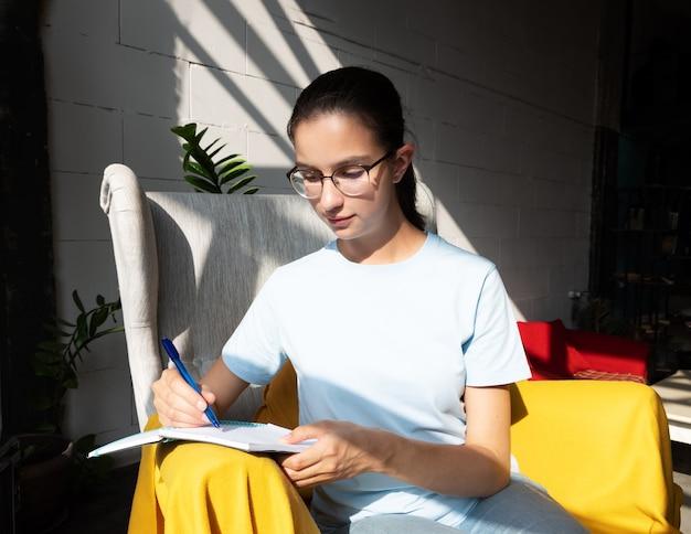 Aluna linda escreve com uma caneta uma tarefa em um caderno enquanto está sentado em uma poltrona em um café com sombras diagonais elegantes, luz forte.