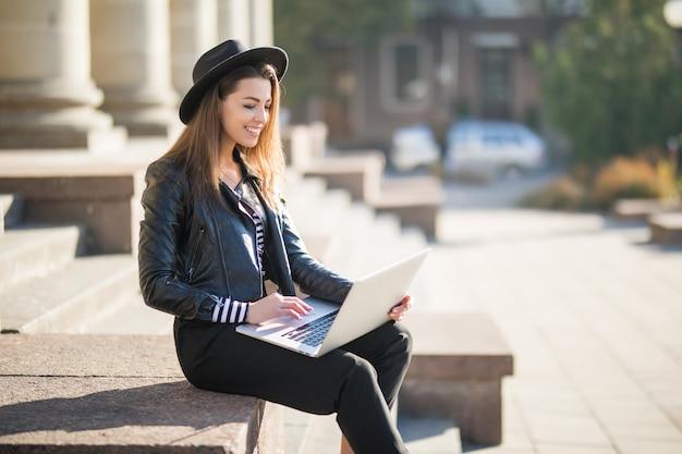 Aluna linda jovem empresária trabalha com o laptop de sua marca