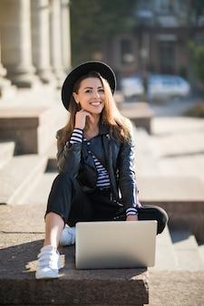 Aluna linda jovem empresária trabalha com seu computador de marca no centro da cidade