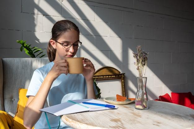 Aluna linda tomando café e escrevendo uma tarefa em um caderno enquanto está sentado em um café