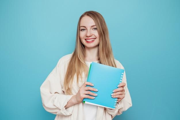 Aluna loira alegre segurando um livro, caderno sorrindo, isolado na parede azul
