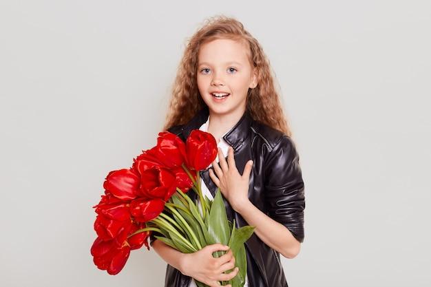 Aluna loira animada com uma jaqueta de couro preta segurando um grande buquê de tulipas vermelhas, surpresa ao receber um presente agradável