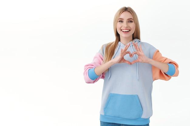 Aluna loira atraente alegre com capuz, mostrando o sinal do coração e sorrindo, expressa amor e ternura