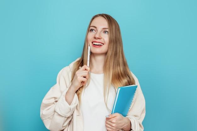 Aluna loira caucasiana pensa e sonha, segura um bloco de notas, caderno, livro isolado em uma parede azul no estúdio. testes, exames, conceito de educação. copie o espaço