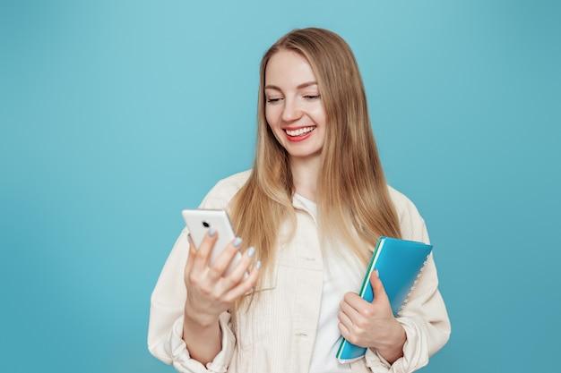 Aluna loira caucasiana segurando um caderno, livro e olha para a tela de um telefone móvel isolado em uma parede azul no estúdio. educação online