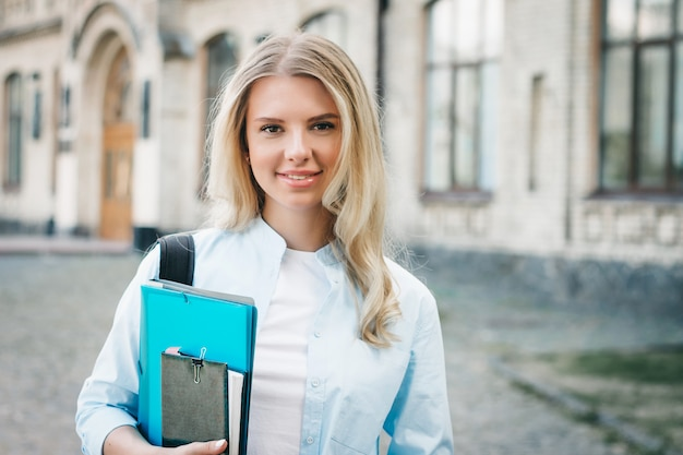 Aluna loira está sorrindo e segurando uma pasta e um caderno nas mãos na universidade