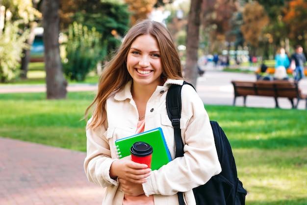 Aluna loira passeios no parque com um notebook e uma xícara de café