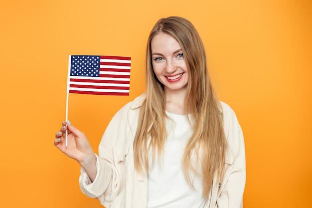 Aluna loira segura uma pequena bandeira americana e sorri