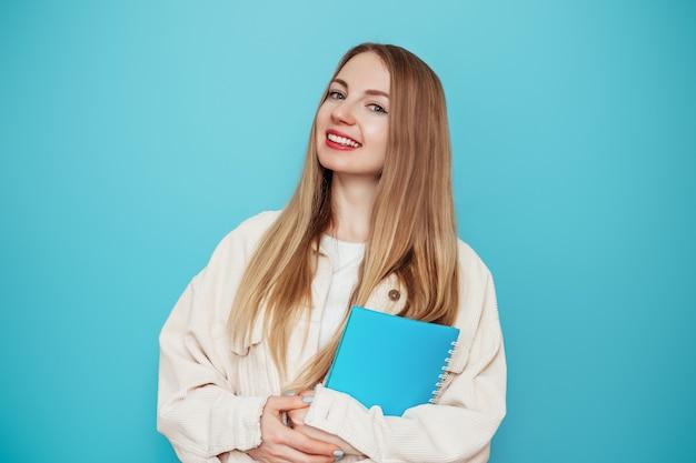Aluna loira segurando um livro, caderno sorrindo, isolado na parede azul