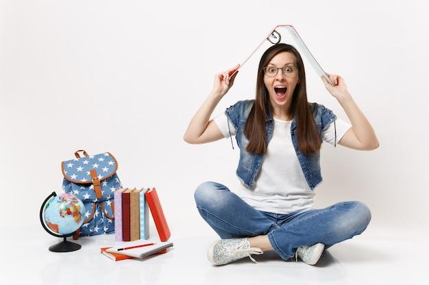 Aluna louca de óculos segura uma pasta vermelha para documentos de papel acima da cabeça, como o telhado, perto do livro escolar da mochila do globo, isolado na parede branca