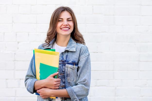 Aluna mantém pastas e um caderno nas mãos e sorri em um fundo de uma parede de tijolos brancos, copie o espaço
