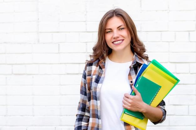 Aluna mantém pastas e um caderno nas mãos e sorri em um fundo de uma parede de tijolos brancos