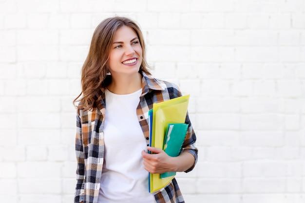 Aluna mantém pastas e um caderno nas mãos e sorri