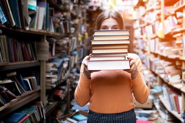 Aluna mantém uma pilha de livros na biblioteca