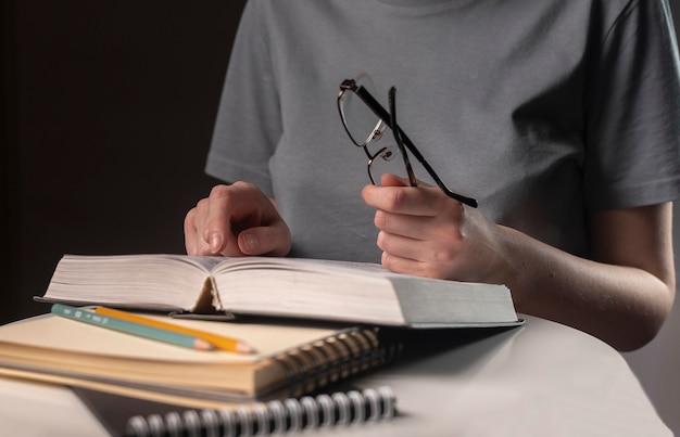 Aluna mãos fecham, segurando óculos e um livro ou livro didático, procurando informações e lendo à noite.