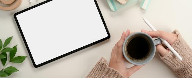Aluna mãos segurando uma caneca de café enquanto trabalhava com mock-se tablet na mesa de estudo