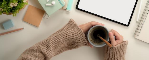 Aluna mãos segurando uma xícara de café enquanto está sentado na mesa de trabalho com mock up tablet e artigos de papelaria
