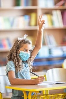 Aluna menina bonitinha com máscara facial de volta à escola durante a quarentena de covid-19.
