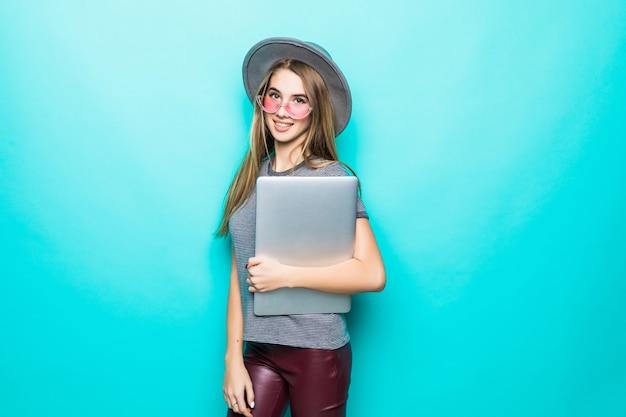 Aluna modelo garota em roupas da moda casuais trabalha relógios em seu laptop isolado no verde
