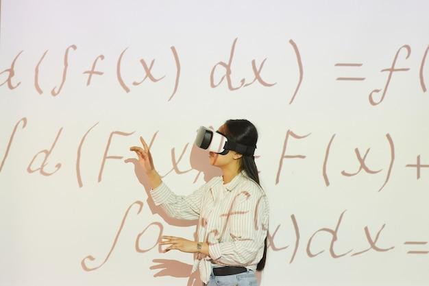 Aluna morena em um fone de ouvido de realidade virtual apontando para a tela de projeção enquanto trabalha com equações matemáticas