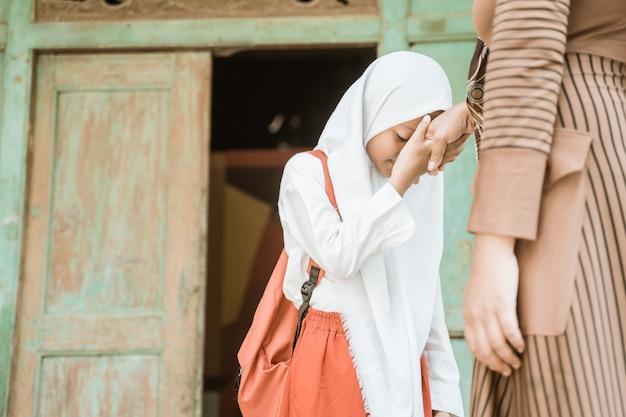 Aluna muçulmana aperta e beija a mão da mãe antes de ir para a escola pela manhã